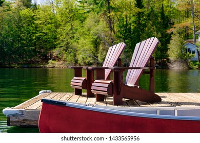 Two Adirondack chairs on a wooden dock facing the blue water of a lake in Muskoka, Ontario Canada. A red canoe is tied to the pier. Across the water cottages nestled between green trees are visible.