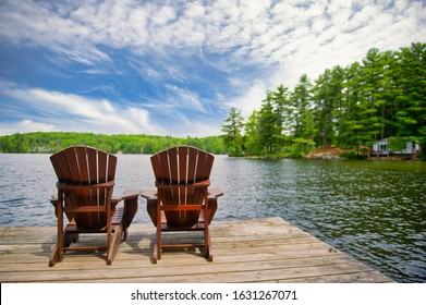Two Adirondack chairs on a wooden dock overlooking a calm lake in Canada. Cottages nestled between green trees are visible across the water.