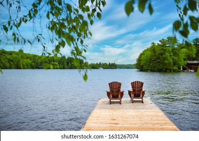 Two Adirondack chairs on a wooden dock facing the blue water of a lake in Canada. Cottages nestled between green trees are visible across the water. In the sky there are clouds.