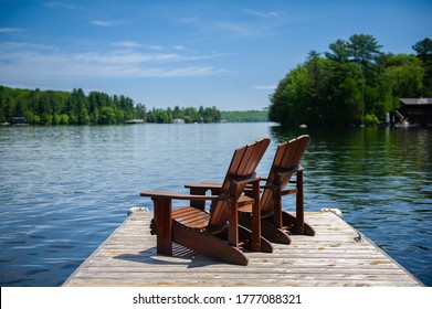 Two Adirondack chairs on a wooden dock overlooking a calm lake.  A cottage nestled between green trees is visible across the water.