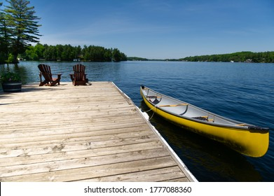 Two Adirondack chairs on a wooden dock facing the blue water of a lake in Muskoka, Ontario Canada during a sunny summer day. A yellow canoe is tied to the dock.