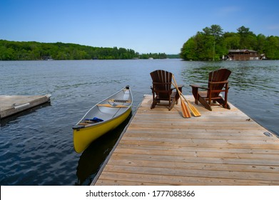 Two Adirondack chairs on a wooden dock facing the blue water of a lake in Muskoka, Ontario Canada. A yellow canoe is tied to the dock while the paddles are next to the chairs.