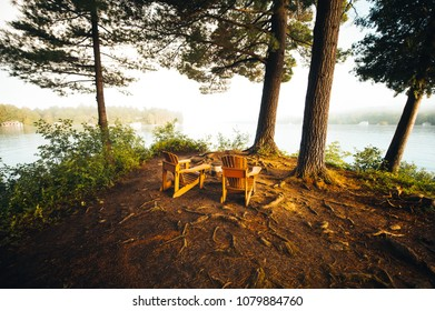 Two Adirondack chairs positioned under trees near a calm lake in Canada. The landscape is foggy.