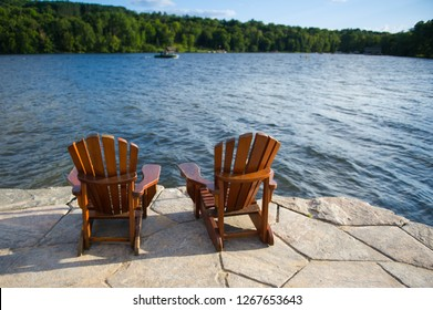 Two Adirondack chairs sit on a stone made pier, facing blue waters of a lake in Muskoka, Ontario Canada. Water sports activities involving a boat are visible in the background.