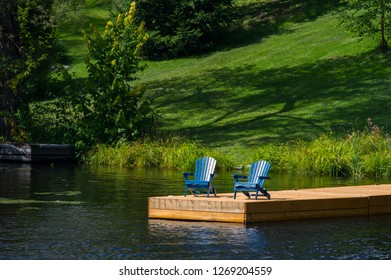 Two Adirondack chairs sit on a wooden dock facing a calm lake. The chairs are facing the camera. In the background the landscape is green.