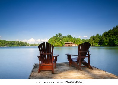 Two Adirondack chairs sit on a wooden dock facing a calm lake. The blue water is reflecting the sky clouds. In the background there's a brown cottage nestled between trees.