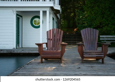 Two Adirondack chairs sit on a wooden dock. In the background there's a white cottage facing the calm blue waters of a lake. Green trees are also visible.