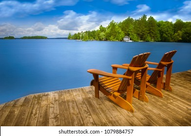Two Adirondack chairs sitting on a wooden dock facing a blue calm lake. Across the water is a white cottage nestled among green trees.