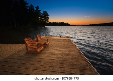 Two Adirondack chairs sitting on a wooden dock facing a blue calm lake during sunset hours