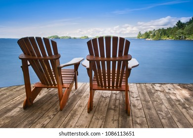 Two Adirondack chairs sitting on a wooden dock facing a blue calm lake. Across the water is a green cabin nestled among green trees.