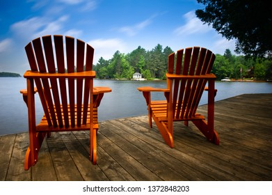 Two Adirondack chairs sitting on a wooden dock facing a blue calm lake. Across the water is a white cottage nestled among green trees. Chair wood is ceder.