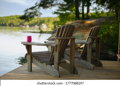 Two Adirondack chairs sitting on a cottage wooden dock facing the calm water of a lake in Muskoka, Ontario Canada. A purple insulated tumbler glass is visible on of of the chairs.