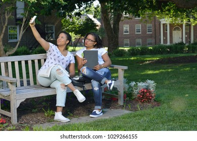 Two. Adorable biracial sisters  sit on bench in shade on campus and take a selfie