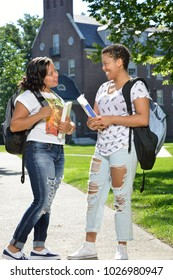 Two. Adorable biracial sisters stand on campus holding textbooks and carrying backpacks stop to chat with each other - education