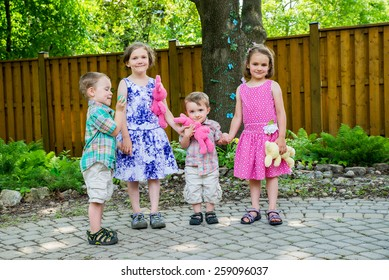 Two adorable boys and happy girls smile holding colorful toy plush bunny rabbits and egg hold hands together during an Easter party outside in a garden.  Part of a series.