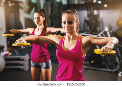Two adorable charming fit girls are doing exercises with small yellow weights alone in gym.
