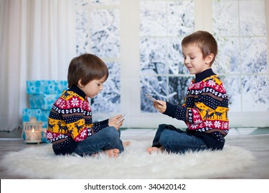 Two adorable children, boy brothers, playing cards at home, wintertime, christmas decoration around them, snowy day behind the window