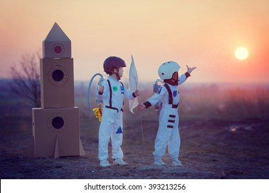 Two adorable children, boy brothers, playing in park on sunset, dressed like astronauts, imagining they are flying on the moon