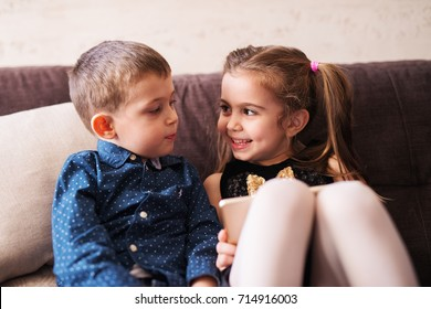 Two adorable children are looking each other while sitting on the sofa.