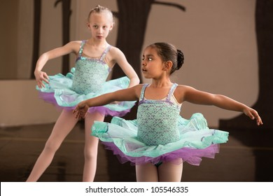 Two adorable children twirling during ballet practice