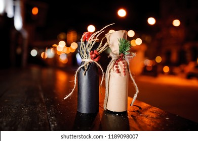 Two adorable christmas decorated gift bottles standing on the wooden bench outside on the background of night street