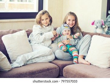 Two adorable european sisters girls holding theur newborn brother having fun in livingroom of theis home. Family with three kids.