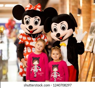 Two adorable girl with mickey and minnie mouse posing in shopping center, smiling and having fun in New York, USA in 2018