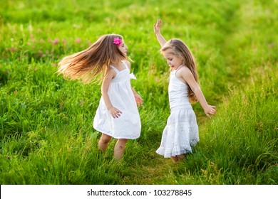 Two adorable girl in white dresses dancing on the meadow