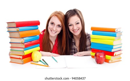 Two adorable girls with piles of books and apples