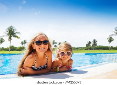 Two adorable girls relaxing at the swimming pool