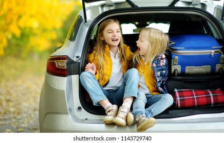 Two adorable girls sitting in a car trunk before going on vacations with their parents. Two kids looking forward for a road trip or travel. Autumn break at school. Family travel by car.