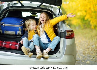 Two adorable girls with a suitcase going on vacations with their parents. Two kids looking forward for a road trip or travel. Autumn break at school. Family travel by car.