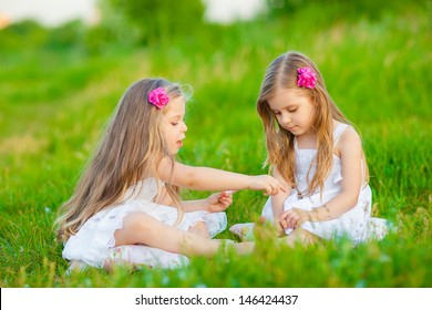 Two adorable girls in white dresses playing on the meadow