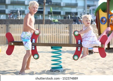 Two adorable happy blond kids, teenager boy and his little baby sister, playing together at outdoors sandy beach playground rocking on a spring seesaw swing
