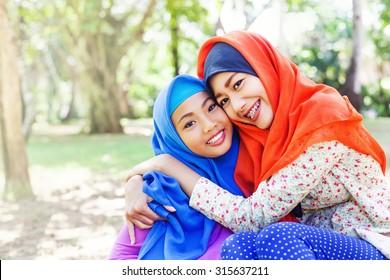 two adorable indonesian muslim sisters