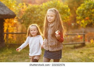 Two adorable kids having fun the park. Autumn concept