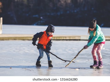 two adorable kids playing ice hockey together. brother and sister imagining playing ice-hockey on frozen river in the park.