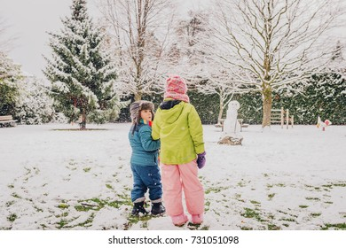 Two adorable kids playing together in snow park, wearing warm winter clothes, back view