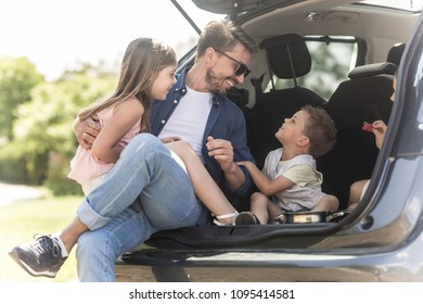 Two adorable kids sitting in a trunk car with father