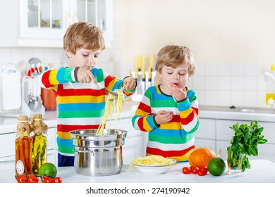 Two adorable little boys preparing healthy meal with spaghetti and fresh vegetables in domestic kitchen, indoors. Sibling children in colorful shirts.