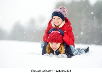 Two adorable little girls having fun together in beautiful winter park. Beautiful sisters playing in a snow. Winter activities for kids.
