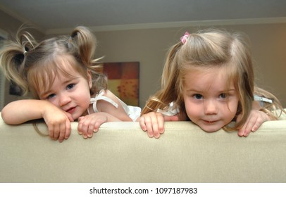 Two adorable little girls peek over the top of the sofa in their home.  Sisters, these two look like trouble.  Youngest has pigtails.
