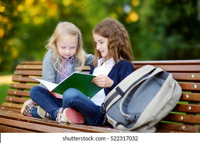 Two adorable little schoolgirls studying in a city park on bright autumn day