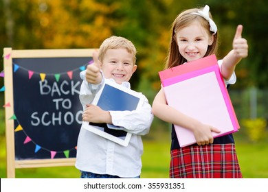 Two adorable little schoolkids feeling very exited about going back to school