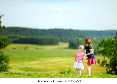 Two adorable little sisters enjoying a beautiful view together on warm and sunny summer day