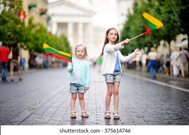 Two adorable little sisters holding Lithuanian flags in Vilnius, the capital of Lithuania