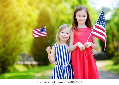 Two adorable little sisters holding american flags outdoors on beautiful summer day. Independence Day concept.