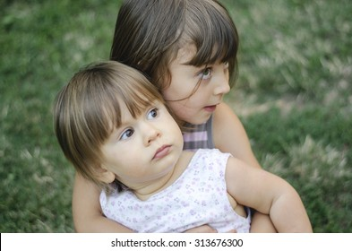 Two adorable little sisters  hugging each other