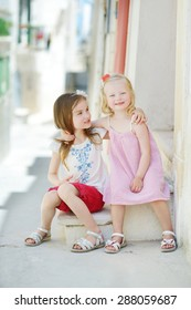 Two adorable little sisters laughing and hugging on warm and sunny summer day in Vieste, Italy