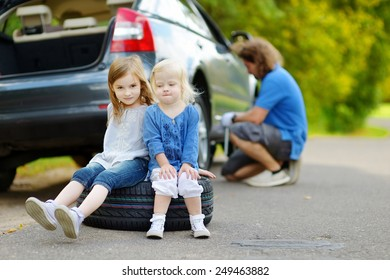 Two adorable little sisters sitting on a tire and waiting while their father is changing a car wheel outdoors on beautiful summer day